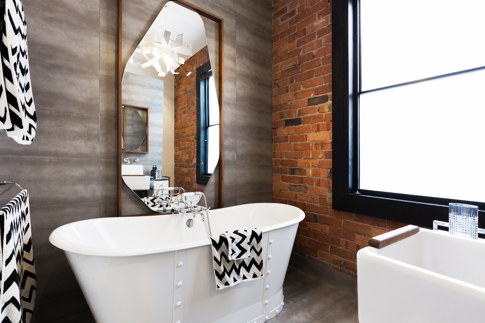 bathroom with textured accent walls in brick and wood paneling