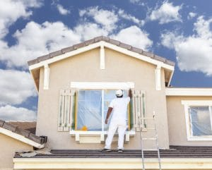 professional painter works on the exterior of the customers home