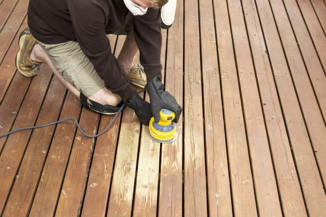 man sanding the deck in preparation of refinishing