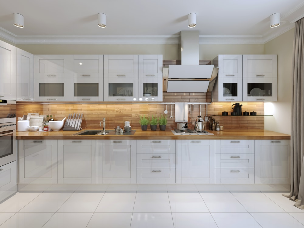 White crown molding is seen in this white kitchen that stops a foot from the ceiling so the crown is visable