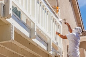 Professional painter sprays the balcony wood work white to match the home trim
