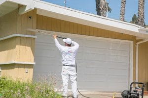 painter power washing a house