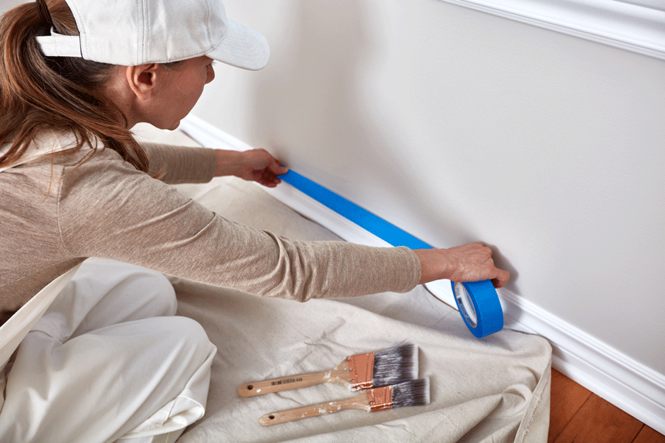 woman applying tape to prepare room to be painted